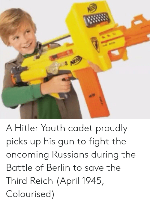 third reich: A Hitler Youth cadet proudly picks up his gun to fight the oncoming Russians during the Battle of Berlin to save the Third Reich (April 1945, Colourised)