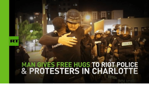 free hug: POLICE  MAN GIVES FREE HUGS TO RIOT POLICE  & PROTESTERS IN CHARLOTTE