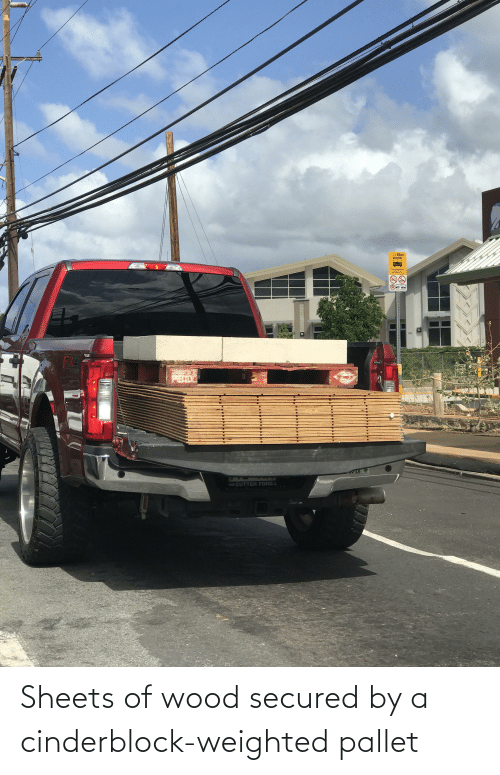 pallet: Sheets of wood secured by a cinderblock-weighted pallet